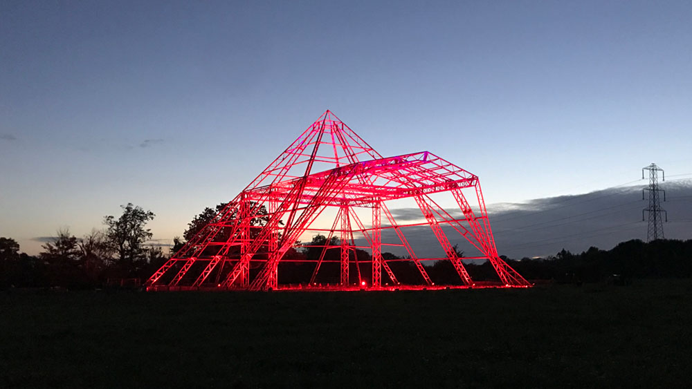 Pyramid Stage at Glastonbury, lit red by Fineline Lighting